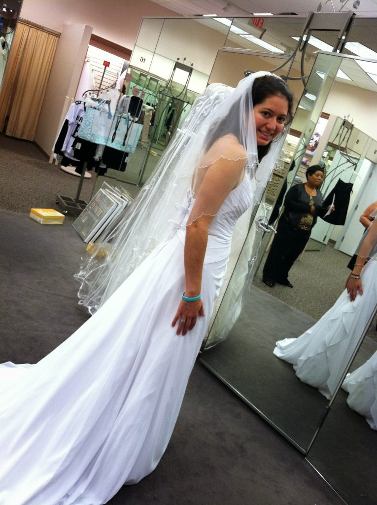 A woman with adrenal insufficiency forces a smile while trying on a wedding dress although she is completely exhausted.