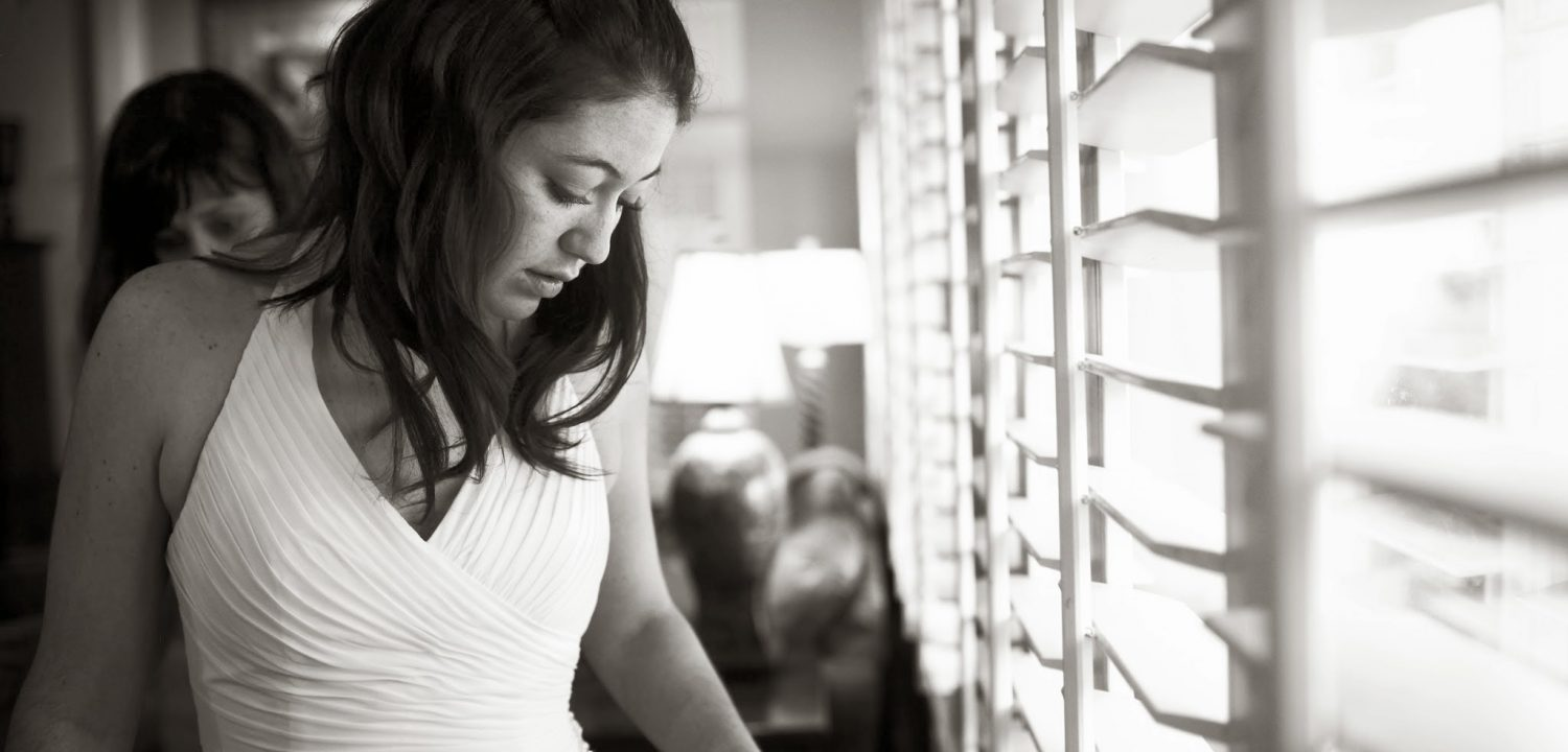 A mother adjusts her daughters wedding dress in preparation for the wedding.