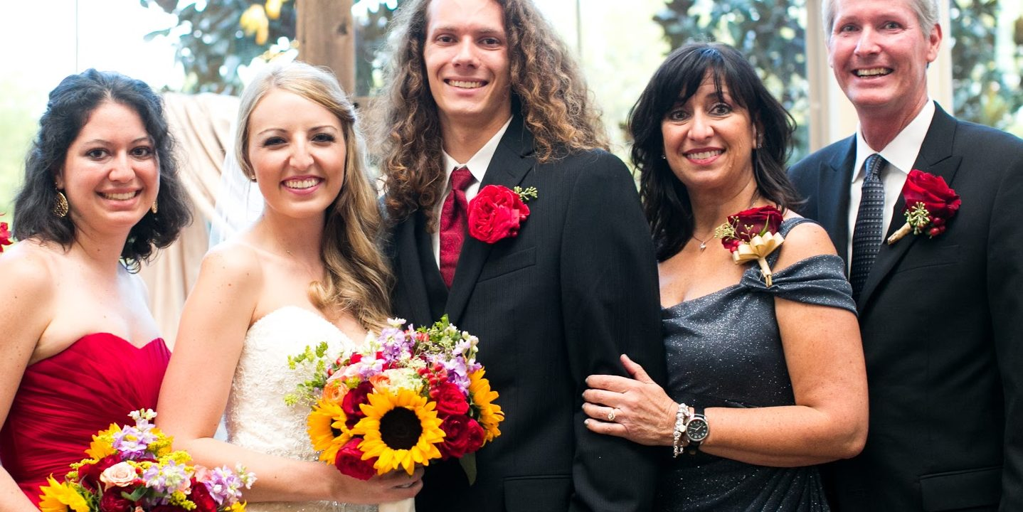 A family smiles for a photo after a wedding.