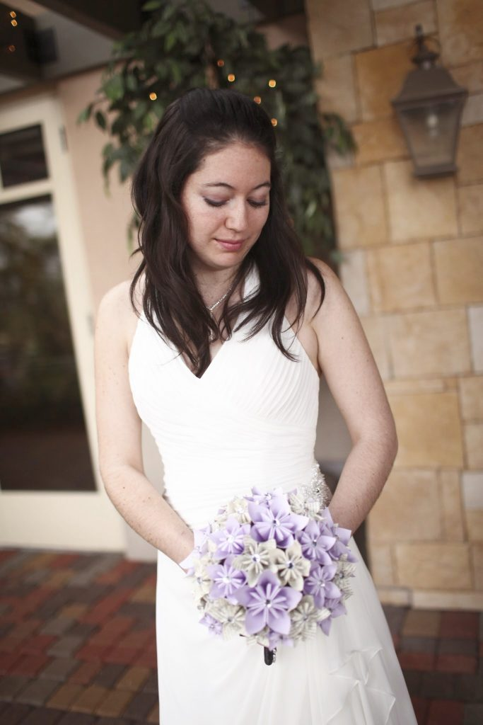 A bride living with Adrenal Insufficiency smiles as she looks down at her wedding flowers.