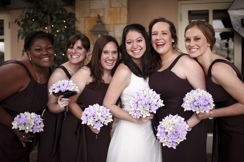 A bride living with Adrenal Insufficiency smiles as she is surrounded by five beautiful bridesmaids all holding their wedding flowers.