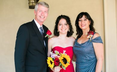 A bridesmaid with adrenal insufficiency stands proudly beside her parents at her brother's wedding.