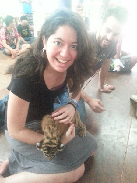 A woman with adrenal insufficiency smiles as she is holding a tiger cub.