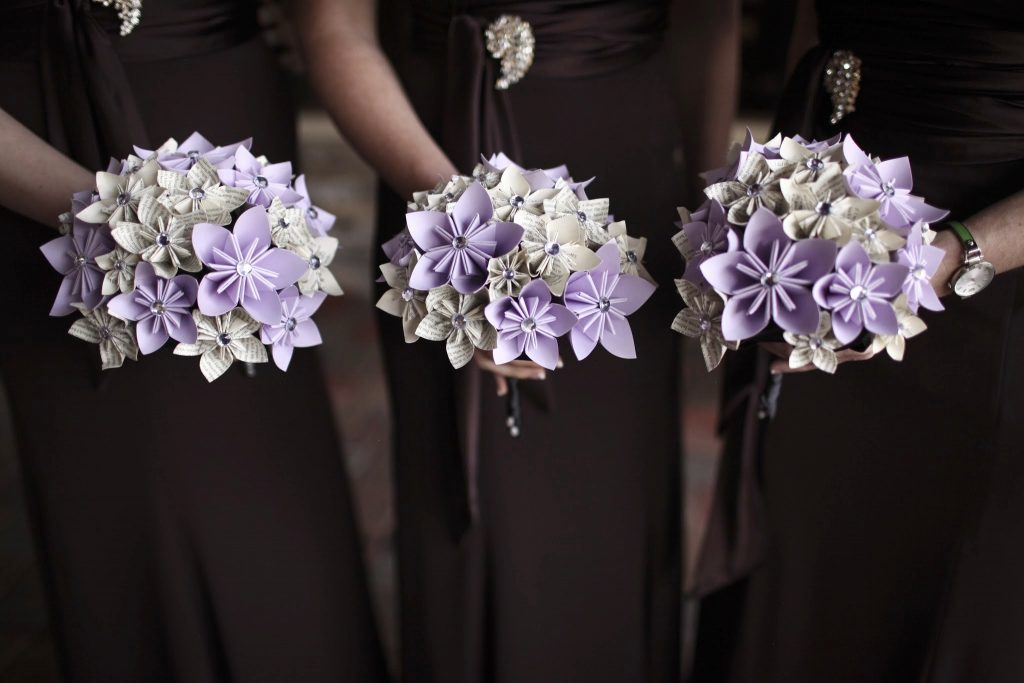 Three beautiful paper wedding flower bouquets on display.