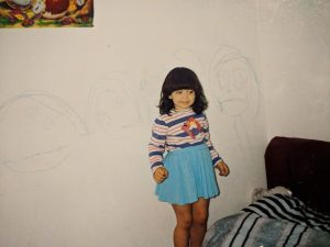 Young Amber Nicole stands in front of one of her first pieces of original art.