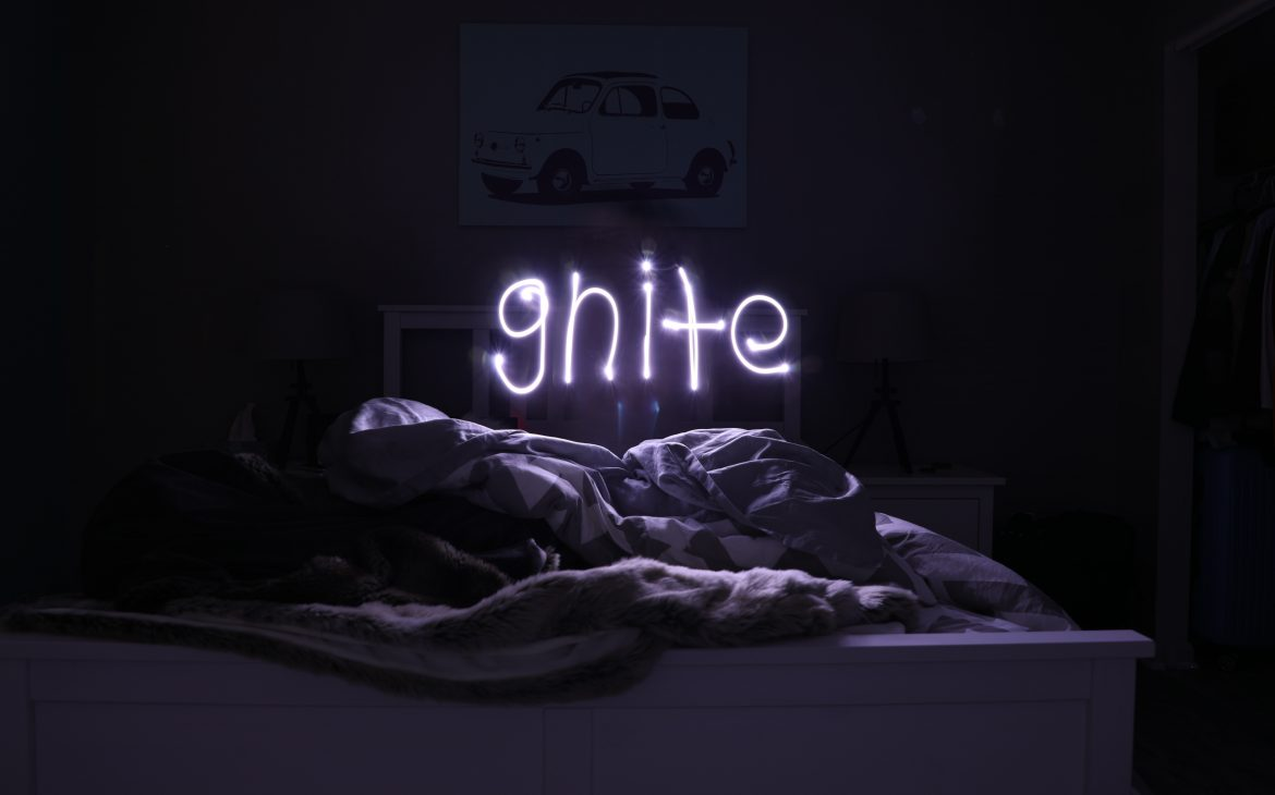 """neon sign with the text """"gnight"""" above a bed"""