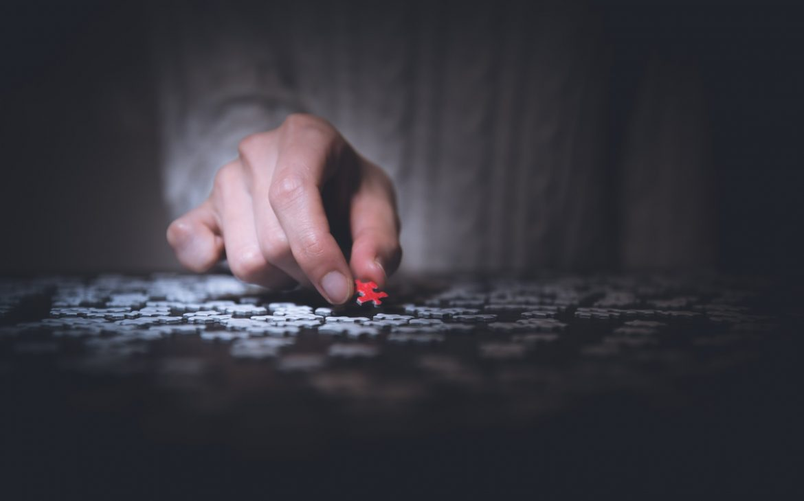 person holding a read jigsaw puzzle piece
