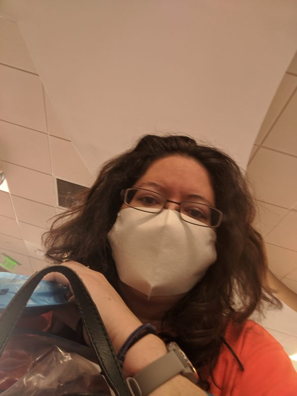 Woman in a wheelchair wearing a mask while in the ER waiting room.