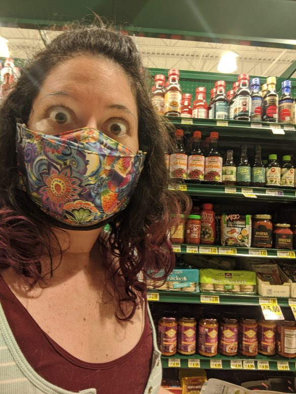 Woman with purple hair wears a cloth face covering while shopping for groceries during COVID-19.